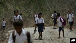 In this Oct. 22, 2018, file photo, students walk on dirt road after school in O'of village in West Timor, Indonesia. Children in this poor area of Indonesia often must walk long distances to school.
