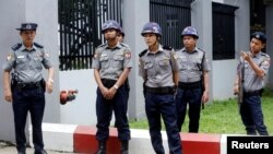 FILE - Police officers stand guard at a building in Yangon, Myanmar, Aug. 9, 2019.