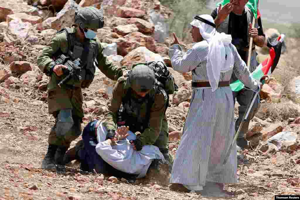 요르단 강 서안지구의 유대인 청착촌에서 이스라엘 병사가 팔레스타인 시위 참가자를 구속했다.