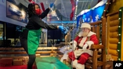 LaToya Booker cleans a transparent barrier between visitors for Santa at a Bass Pro Shop in Bridgeport, Conn., Nov. 10, 2020.