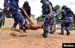 Ugandan riot policemen detain a supporter of presidential candidate Robert Kyagulanyi, also known as Bobi Wine, in Luuka district, eastern Uganda, Nov. 18, 2020.