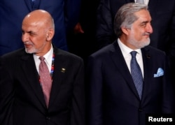 FILE - Afghan President Ashraf Ghani, left, and Afghan Chief Executive Abdullah Abdullah are pictured at a NATO summit in Warsaw, Poland, July 8, 2016.