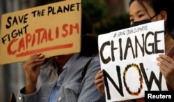 Demonstrators protest during a climate change strike in front of the St. Joseph Cathedral in Hanoi, Vietnam Sept. 27, 2019.