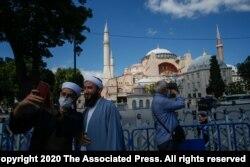 Para turis berfoto di depan Hagia Sophia di Istanbul, Turki (11/7).
