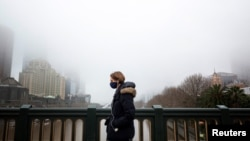 A person in a protective face mask walks along the Princes Bridge amidst a lockdown in response to an outbreak of the coronavirus disease (COVID-19) in Melbourne, Australia, July 17, 2020. (AAP Image/Daniel Pockett via Reuters)