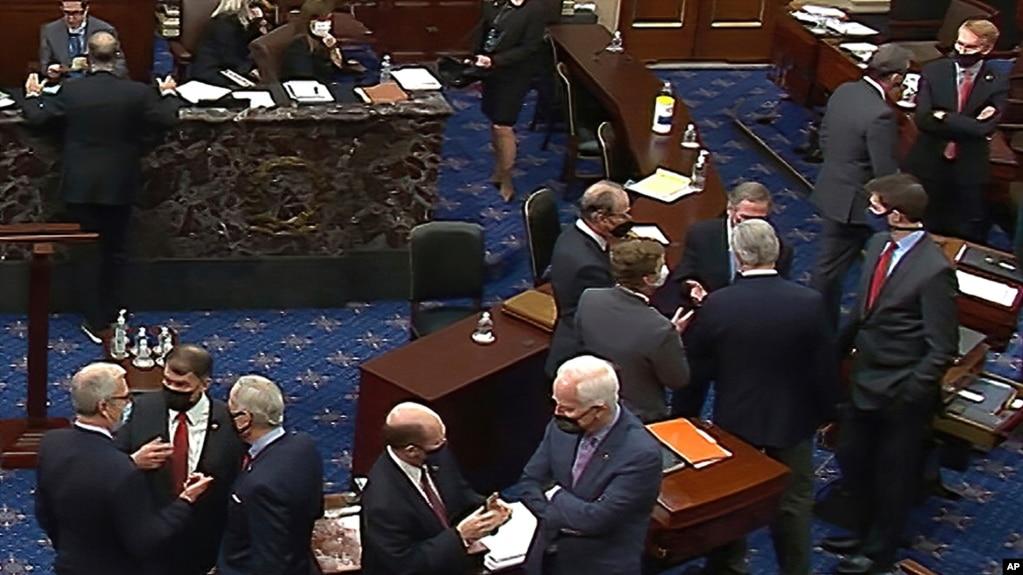 资料照片:参议院电视截屏显示共和党参议员和幕僚在针对特朗普总统的第二次弹劾审判的会场交谈。(2021年2月13日)(photo:VOA)