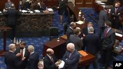 资料照片:参议院电视截屏显示共和党参议员和幕僚在针对特朗普总统的第二次弹劾审判的会场交谈。(2021年2月13日)