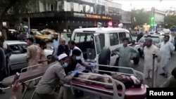 A screen grab shows people carrying an injured person to a hospital after an attack at Kabul's airport, in Kabul, Afghanistan Aug. 26, 2021. An Islamic State offshoot claimed responsibility for deadly suicide attacks outside the airport.