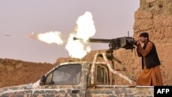 FILE - A member of an anti-Taliban militia fires a machine gun during a fight with Taliban insurgents in Mukhtar, on the outskirts of Lashkar Gah, Afghanistan, March 28, 2021. Government forces battled a Taliban assault on Lashkar Gah on July 31, 2021,