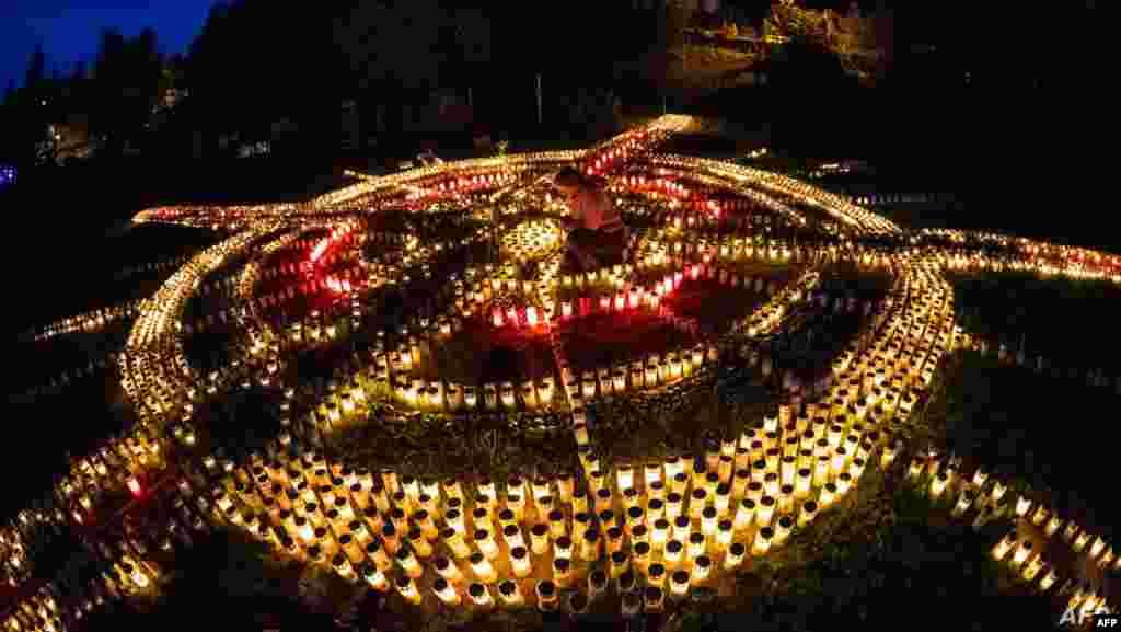 독일 젤라 메흐리스(Zella-Mehlis)에서 남성이 신종 코로나바이러스 감염증(COVID-19)으로 숨진 희생자 8,000명을 애도하기 하기 위해 촛불을 켜 거대한 십자가 모형을 만들고 있다.