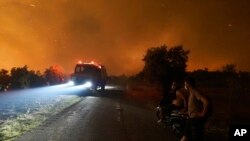 Flames burn a forest during a wildfire in Skepasti village on the island of Evia, about 150 kilometers (93 miles) north of Athens, Greece, Aug. 5, 2021. Wildfires rekindled outside Athens and forced more evacuations around southern Greece.