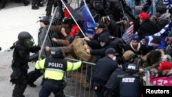 Pro-Trump protesters tear down a barricade as they clash with Capitol Police during a rally to contest the certification of the 2020 U.S. presidential election results by the U.S. Congress, at the U.S. Capitol Building in Washington, Jan. 6, 2021.
