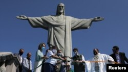 Brazil's Environment Minister Ricardo Salles, accompanied by authorities and clergy, cuts a ribbon during the reopening ceremony of the Christ the Redeemer statue, in Rio de Janeiro, Brazil, Aug. 15, 2020.