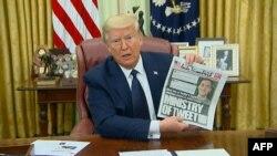 El presidente de los Estados Unidos, Donald Trump, muestra la portada de un diario local que aborda el tema de las redes sociales durante la firma del decreto, el pasado 28 de mayo.