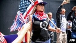 (FILES) In this file photo taken on May 01, 2020 conspiracy theorist QAnon demonstrators protest during a rally to re-open California and against Stay-At-Home directives in San Diego, California. - YouTube said October 15, 2020 it was tightening…