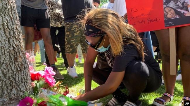 示威者星期六(6月13日)在富勒遗体被发现的树下放花放蜡烛。富勒遗体是6月10日发现的