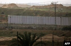 FILE - A picture taken in Rafah in the southern Gaza Strip at the border with Egypt shows a concrete wall under construction on the Egyptian side of the border, Feb. 19, 2020.