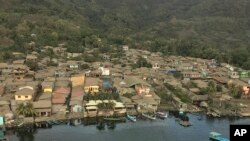 In this Jan. 21, 2020, photo provided by the Philippines Office of Civil Defense, volcanic ash covers roofs of houses near Taal volcano in Batangas province, southern Philippines.