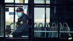 A security guard wearing a mask rides on an empty bus in Beijing, Sunday, Feb. 9, 2020. China's virus death toll on Sunday have surpassed the number of fatalities in the 2002-2003 SARS epidemic, but fewer new cases were reported in a possible sign…