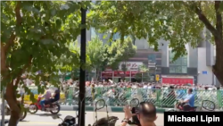 In this screen grab from video shared on social media, Iranians march chanting anti-government slogans on a street in central Tehran, July 26, 2021.
