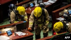 Members of the fire brigade perform tests in the main chamber of the Legislative Council after pan-democrat lawmakers hurled an odorous liquid during the third reading of the national anthem bill in Hong Kong on June 4, 2020.