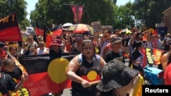 FILE - People carry Australian Aboriginal flags during a demonstration on Australia Day in Sydney, Jan. 26, 2019.