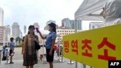 지난 8월 북한 평양역 입구에서 역무원이 신종 코로나바이러스 방역을 위해 승객들의 체온을 재고 있다.