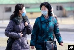 People wear masks to protect from a new coronavirus as they walk through the Kwangbok Street in Pyongyang, North Korea, Feb. 26, 2020.