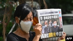 A supporter of two executives from Hong Kong's pro-democracy Apple Daily newspaper, chief editor Ryan Law and CEO Cheung Kim-hung, holds up a copy of the paper during a protest outside court on June 19, 2021, after the two were charged with collision.