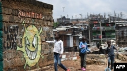 A young boy reads out the message from an informational mural warning people about the risk of COVID-19 in a slum in Nairobi, Kenya, April 22, 2020.