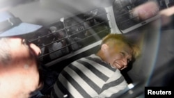 FILE - Satoshi Uematsu, suspected of a deadly attack at a facility for the disabled, is seen inside a police car as he is taken to prosecutors, at Tsukui police station in Sagamihara, Kanagawa prefecture, Japan, in this photo taken by Kyodo July 27, 2016.