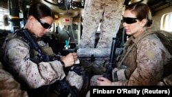 资料照片:美国海军陆战队第八团第一营的妇女接触事务队队长希娜·亚当中士(左)与医务兵珊农·克罗利坐在装甲车内准备离开她们位于阿富汗赫尔曼德省的基地,外出执行任务。(2010年11月13日)