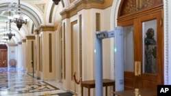 FILE - Members of the House of Representatives must now pass through a security check with metal detectors before entering the chamber, a new safety measure put into place after a mob stormed the Capitol January 6, in Washington, Jan. 27, 2021.