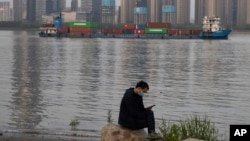 In this Monday, April 13, 2020, photo, a man wearing a mask against the new coronavirus checks his phone as a container ship cruises along the Yangtze River in Wuhan in Central China's Hubei province. China's exports fell further in March compared…