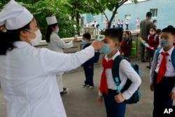 资料照:朝鲜首都平壤一所小学的学生带着口罩接受体温检测。(2020年6月3日)
