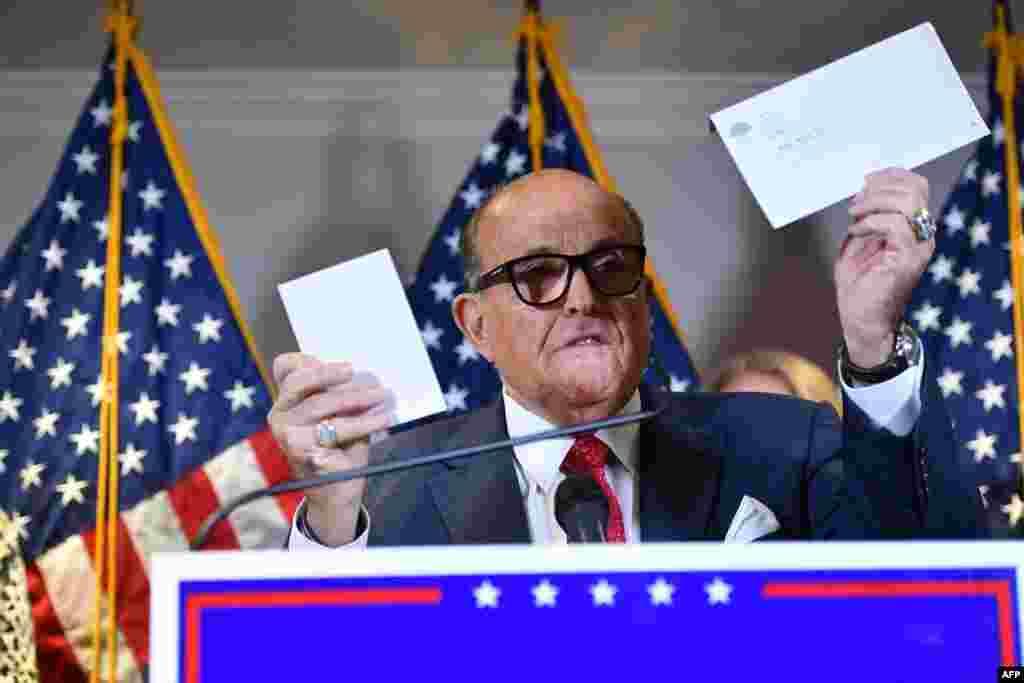 도널드 트럼프 미국 대통령의 개인 변호사인 루돌프 줄리아니 전 뉴욕 시장이 공화당 전국위원회 본부에서 대선 불복 소송에 관한 기자회견을 하는 도중 우편투표 봉투를 들어보이고 있다.