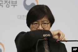 South Korean Centers for Disease Control director Jung Eun-kyeong shows a preferred coughing posture during a press conference at the government complex in Seoul, South Korea, Jan. 23, 2020.