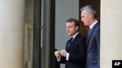French President Emmanuel Macron, left, and NATO Secretary-General Jens Stoltenberg walk out of the lobby after a meeting at the Elysee Palace in Paris, Nov. 28, 2019.