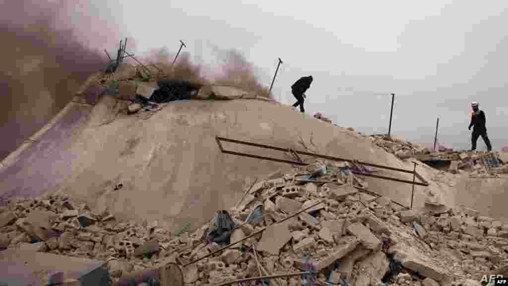 시리아 알레포에서 정부군의 공습이 있은 후 '화이트 헬멧츠(White Helmets)' 소속 대원이 무너진 건물 현장에서 시신을 수색하고 있다.
