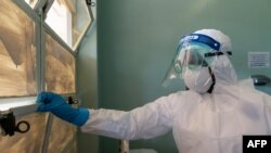 FILE - A medical staff member wears protective equipment while closing a window at the Wilkins Infectious Diseases Hospital in Harare, March 11, 2020.