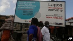 Pedestrian walk past a sign telling resident to call phone numbers if the have coronavirus symptoms in Lagos Nigeria, Tuesday May 12, 2020. Though Nigeria began a phased easing of its strict lockdown measures on Monday, 4 2020 it's confirmed cases…