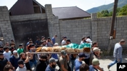 People carry the body of Zelimkhan Khangoshvili, a Chechen Georgian who fought against Russia in the Second Chechen War and had links with Georgian intelligence, during his funeral in Duisi village, Georgia, Aug. 29, 2019.