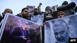 Protesters shout slogans against the United States and Israel as they hold posters with the image of top Iranian commander Qasem Soleimani, who was killed in a US airstrike in Iraq, and Iranian President Hassan Rouhani during a demonstration in the…