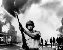 FILE - In this July 1967 file photo, a National Guardsman stands at a Detroit intersection during riots in the city.