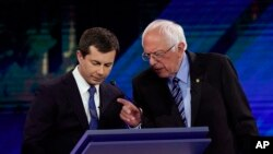 Democratic presidential candidates South Bend Mayor Pete Buttigieg, left, and Sen. Bernie Sanders talk during a break, Sept. 12, 2019, during a Democratic presidential primary debate in Houston.