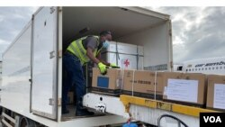 A Zimbabwe health official transfers donated Sinopharm COVID-19 vaccine from a plane from China into a government truck, at Robert Gabriel Mugabe International Airport, Feb. 15, 2021. (Columbus Mavhunga/VOA)