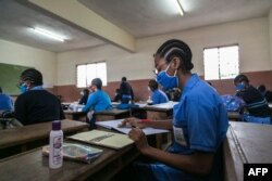Students wear face masks as a preventive measure against the spread of the COVID-19 coronavirus in their classroom at the Jean Benoit College in Yaoundé, Cameroon, on June 1, 2020.