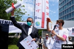 Generalni direktor Svjetske zdravstvene organizacije (WHO) Tedros Adhanom Ghebreyesus drži pismo koje mu je predao član doktora za XR (pobunu protiv izumiranja) u kojem ga poziva da poduzme mjere u vezi s klimatskim promjenama, u Ženevi, Švicarska, 29. maja 2021. godine.