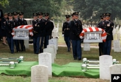 FILE - An Army honor guard carries the caskets of Julian Bartley Jr., left, and his father Julian Bartley Sr. during funeral services at Arlington National Cemetery in Arlington, Va., Aug. 18, 1998.