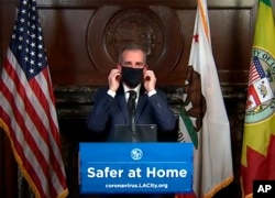 This still image taken from a live stream provided by Office of Mayor Eric Garcetti showing Los Angeles Mayor Garcetti displaying putting on a protective face mask during his daily news conference in Los Angeles, April 1, 2020.